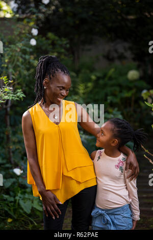 Grandmother and granddaughter smiling at each other in a garden - Stock Image