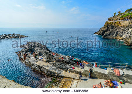 Swimmers and tourists enjoy a sunny summer day on the Italian Riviera at the rocky coast of Manarola Cinque Terre, - Stock Image