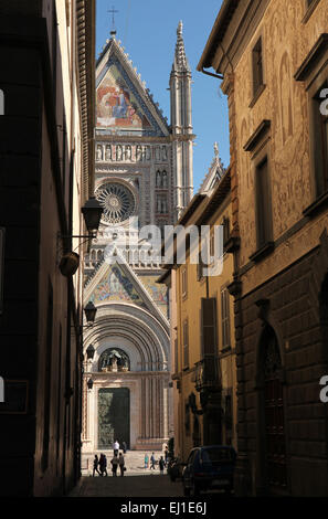 People walk in front of the Orvieto Cathedral (Duomo di Orvieto) in Orvieto, Umbria, Italy. - Stock Image