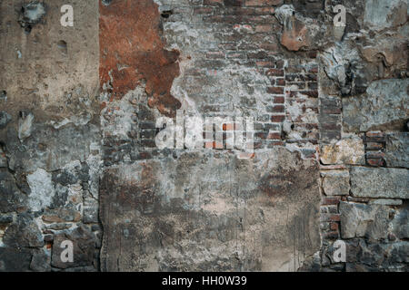 Mixed texture of stone, concrete, cement and bricks on the wall of old park in Barcelona on sunny day - Stock Image