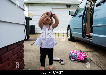 A 2-year old takes a drink from a juice box on a warm day outside a van with the door open. - Stock Image