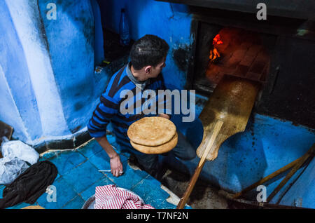 Chefchaouen, Morocco : A man bakes flat bread at a traditional oven in the blue-washed medina old town. - Stock Image