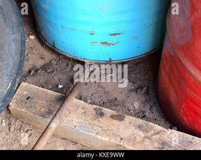 Lifting up heavy metal barrel using iron lever supported on wooden log - Stock Image