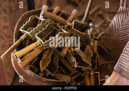 A woven basket holds a number of sistrums used in church services, inside a rock church at Wukro, Ethiopia. The - Stock Image
