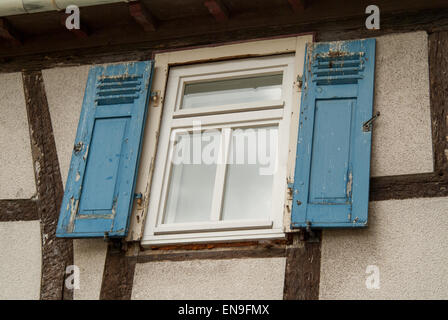 weathered blue shutters and side of building - Stock Image