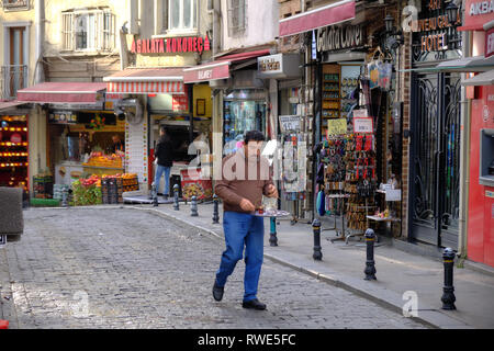 Local man carrying a tray to deliver morning tea to local business in Galata area of Istanbul Turkey - Stock Image