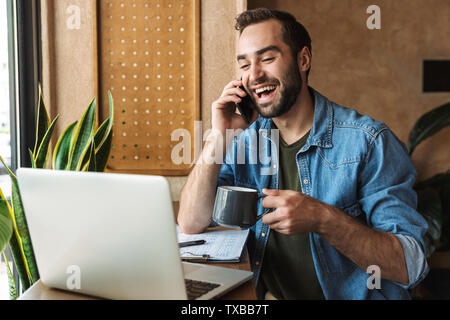 Photo of handsome laughing man wearing denim shirt talking on cellphone and drinking coffee with laptop while working in cafe indoors - Stock Image