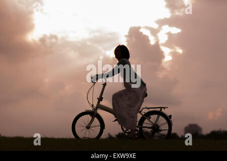 Young woman riding a bike and looking away, - Stock Image