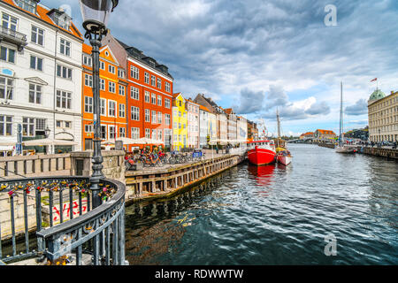 Tourists sightsee, shop and dine at sidewalk cafes on an autumn day on the 17th century waterfront canal Nyhavn in Copenhagen, Denmark. - Stock Image
