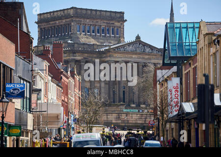 Harris Museum, Art Gallery and Library in Preston, UK, seen from the end of Friargate, framed by out-of-fous shops and pedestrians in the foreground. - Stock Image
