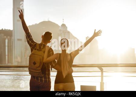 Happy couple with raised arms greeting sunset at big city. Hong-Kong, China - Stock Image