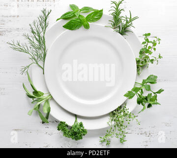 Empty plate with herbs on wooden table - Stock Image