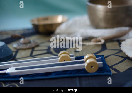 A wo healing tuning forks with Tibetan singing bowls and tingsha in the background. - Stock Image
