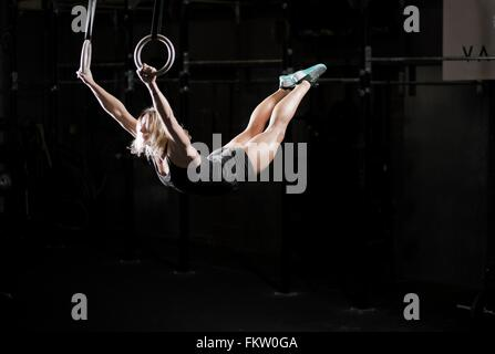 Young woman swinging on gym rings in dark gym - Stock Image