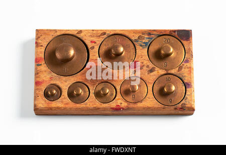 Old brass metric weights in a tray of wood - Stock Image