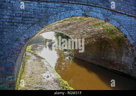 Barges or narrow boats seen through a canal bridge on the Llangollen Canal Cheshire England UK - Stock Image