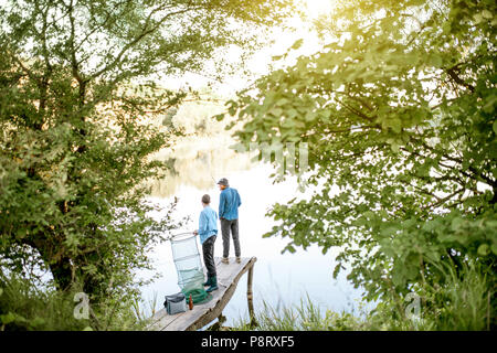 Two male friends preparing for fishing standing with fishing net and rod on the wooden pier during the morning light on the lake - Stock Image