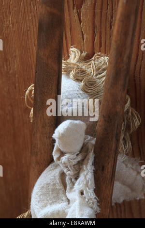 A rag doll is stuck in the backrest of a wooden chair. - Stock Image