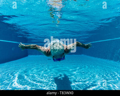 Active people old senior man swimming underwater on a blue pool water with dive mask - play and stay healthy with sport activity for mature retired ma - Stock Image