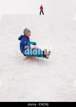 small laughing boy sledging fast down a steep hill with small girl standing at top of hill in background - Stock Image