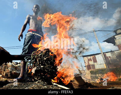A youth burns old old cables to recycle the copper wire inside in Freetown, Sierra Leone - Stock Image