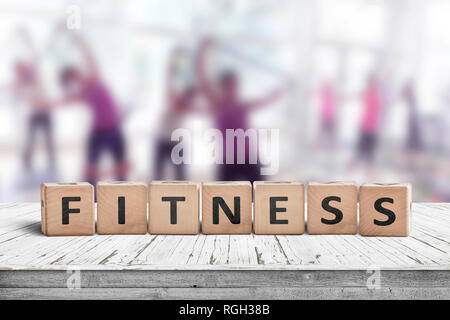 Fitness sign on a table in a gym with women training in the background - Stock Image
