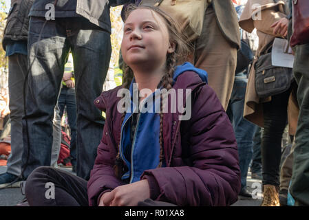 London, UK. 31st October 2018. Swedish schoolgirl Greta Thunberg sits in the crowd of people blocking the roadway in front of Parliament after making the 'Declaration of Rebellion' against the British Government for its criminal inaction in the face of climate change catastrophe and ecological collapse. They listened to speeches by George Monbiot and Green Party MP Caroline Lucas and there were songs and poems. A number of activists brought large wreaths and lay down with them, with several lock-ons. Police tried to clear the road, but the protesters ignored them, taking a show of hands to rem - Stock Image