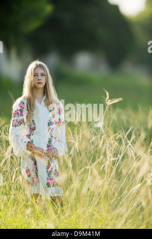 Portrait of young girl in the field,wearing Slavic costume - Stock Image