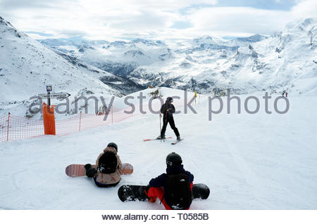 A skier and two snowboarders get ready to descend from the Sommet Aiguille, at the ski resort in Sainte-Foy-Tarentaise, Auvergne-Rhône-Alpes region in - Stock Image