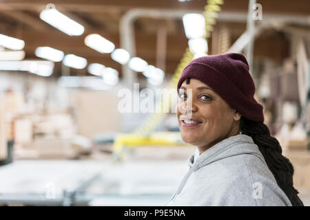 Portrait of a Black woman carpenter in a large woodworking shop. - Stock Image