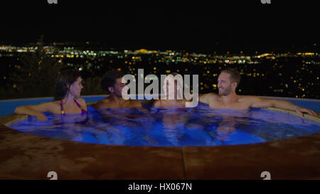 Smiling couples sitting in illuminated hot tub overlooking cityscape at night - Stock Image