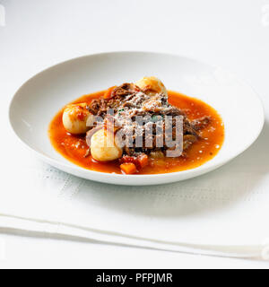 Gnudi (pasta and meat sauce with ricotta dumplings) in white bowl, close-up - Stock Image