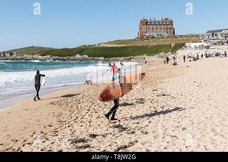 Surfers carrying their surfboards walking across Fistral Beach in Newquay in Cornwall. - Stock Image