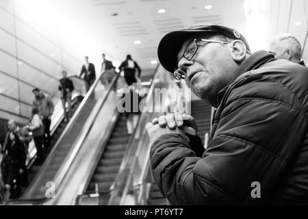 West Ham United Football Club fan waiting for a train wearing a flat cap and team badge, in black and white. - Stock Image