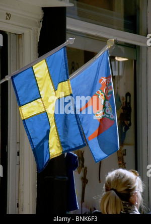 Stockholm, Sweden. Blond woman walking past a Swedish flag and a flag with a Dala horse - Stock Image