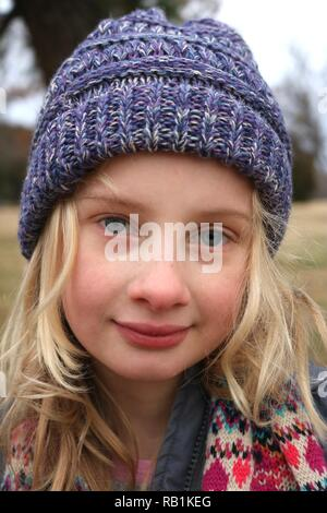 Portrait of a young blond blue eyed girl wearing a purple beanie hat in the cold - Stock Image