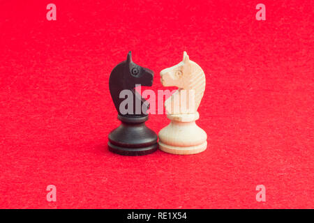 White horse and black horse, traditionally confronted in chess game, have reconciled. Image in isolated red background. - Stock Image