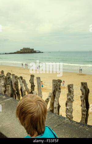 Young boy looking at Fort National from a beach, Saint Malo, Brittany, France. - Stock Image