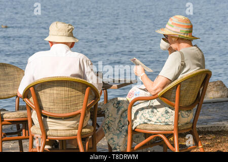 LAKE GARDA, ITALY - SEPTEMBER 2018: Mature man and woman sitting at a lakeside table in Garda on Lake Garda relaxing and having a cup of tea - Stock Image