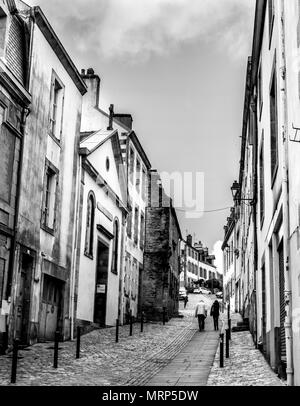 Two people walking up one of the steeper historic streets in Quimper, Brittany, France. B&W - Stock Image