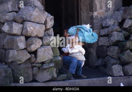 A young, indigenous Tzutujil Maya girl sitting outside her house with a baby. San Lucas Tolimán, Lake Atitlan, Guatemala. - Stock Image