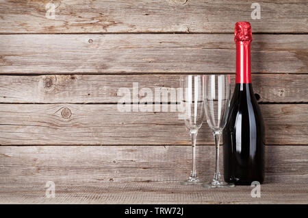 Champagne bottle and glasses in front of wooden wall. With space for your text - Stock Image