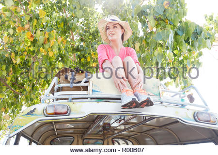 Young woman sitting on tour bus roof - Stock Image
