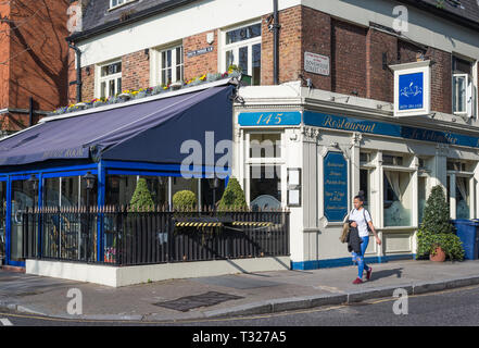 Young woman walking past Le Colombier French restaurant in Dovehouse Street, Chelsea, London, England, UK - Stock Image