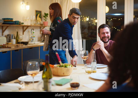 Friends talking, man setting table at dinner party - Stock Image