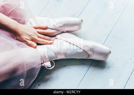 Hands of ballerina in pink tutu skirt puts on pointe shoes on leg in white light hall. Young classical ballet dancer girl in dance class - Stock Image