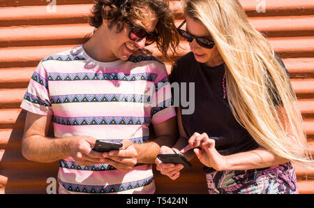 Millennial young people couple together using both cellular mobile phone looking the devices - coloured clothes for summer lifestyle - technology and  - Stock Image