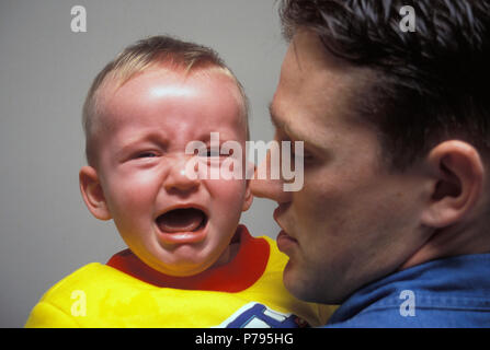 father holding crying baby - Stock Image