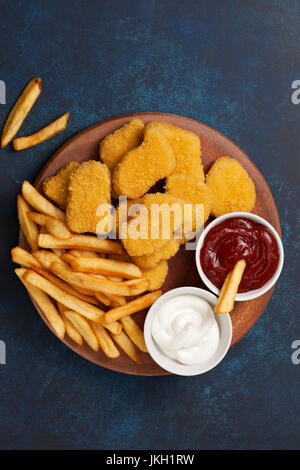 Chicken nuggets and french fries, sauces of ketchup and mayonnaise on a blue background. view from above - Stock Image
