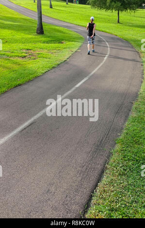 Woman walking exercising on the cycling and walking track in Fannie Bay, Darwin, Northern Territory, Australia. - Stock Image